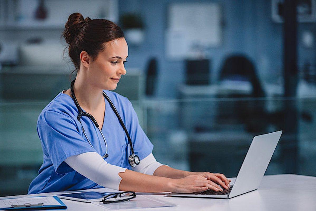 Eine junge Ärztin im Krankenhaus greift mit dem Laptop auf die elektronische Patientenakte zu.